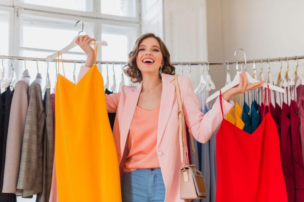 Moça com roupas coloridas em loja de roupas